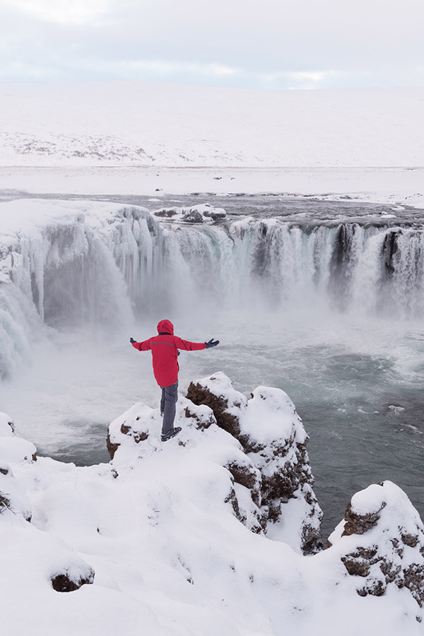 Person enjoying the amazing nature of Iceland's waterfalls in winter. Winter is a great time to visit Iceland if your'e not afraid of the cold! #travel #iceland
