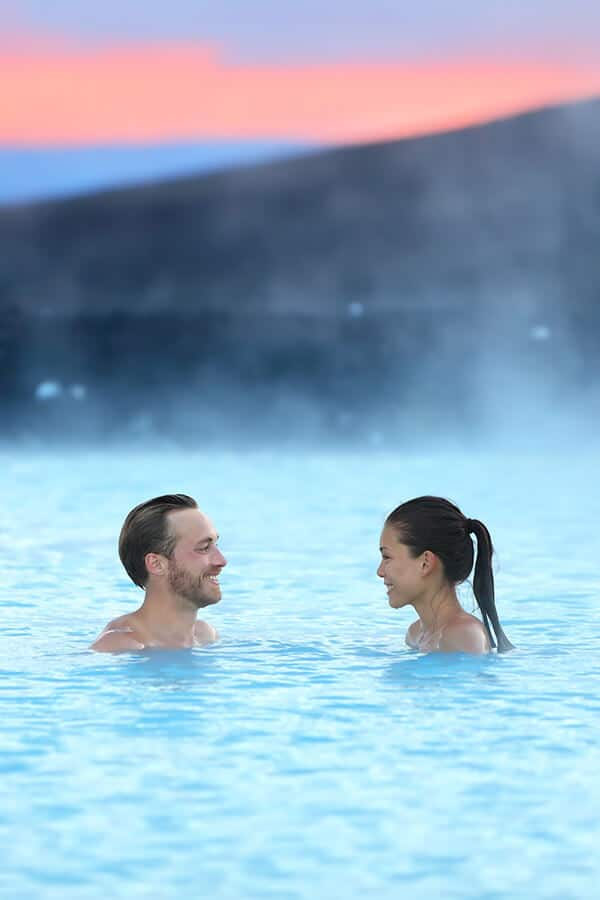 Couple enjoying a romantic dip in an Icelandic hot spring, one of the best things to do in Iceland in winter! #travel #iceland #hotspring