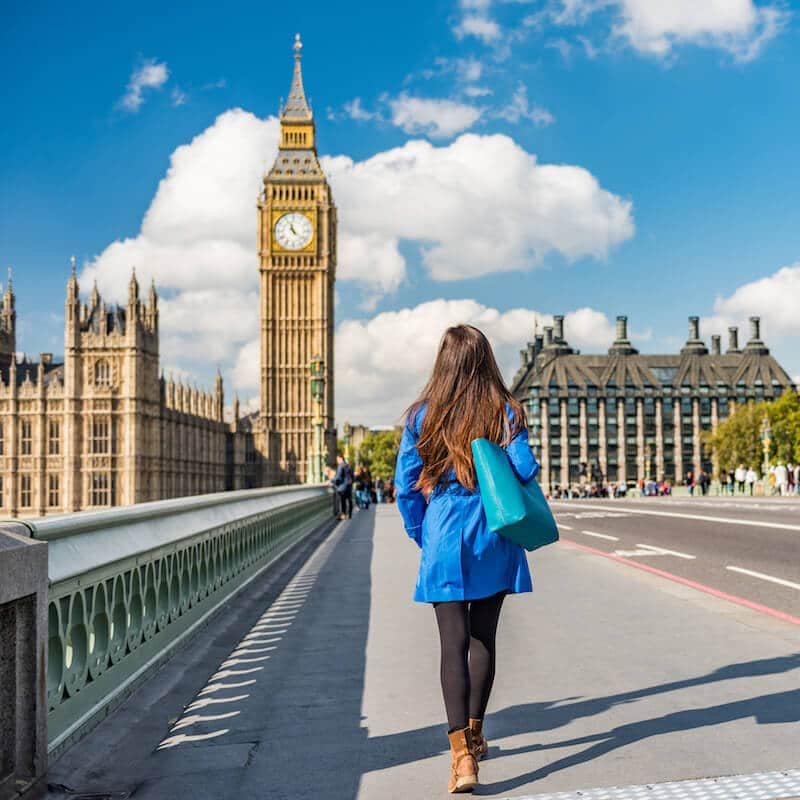 Girl walking in London with view of Big Ben and Westminster Abbey, two must-see attractions in London. Read the perfect one day guide to London! #london #travel