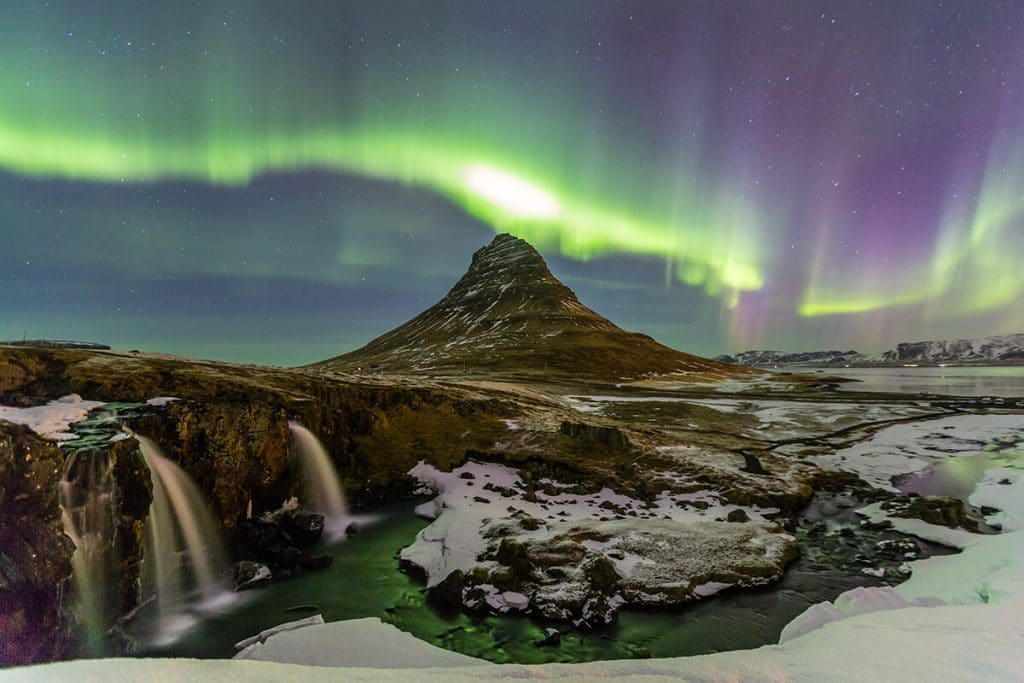 Northern Lights above Kirkjufell. Read what you need to know about visiting Iceland to see the Northern Lights. #travel #iceland