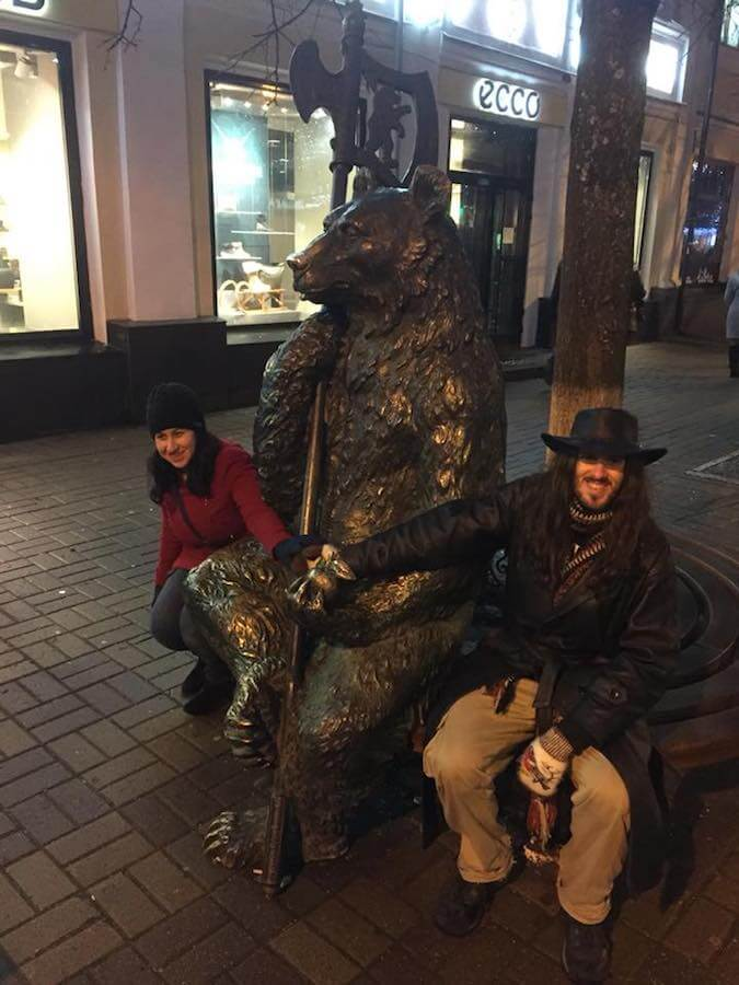 Couple touching one of the famous bear statues in Yarolsavl, Russia.