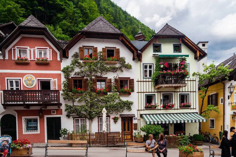 Beautiful houses with wooden shutters and flower boxes in the windows along the main square of Hallstatt, Austria. #travel #hallstatt