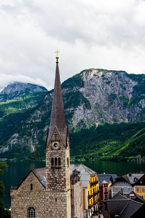 Beautiful view of the church in Hallstatt, Austria with a stunning view of the mountains surrounding the Hallstätter See. Hallstatt is considered one of the most beautiful places to visit in Austria! #Austria #Hallstatt