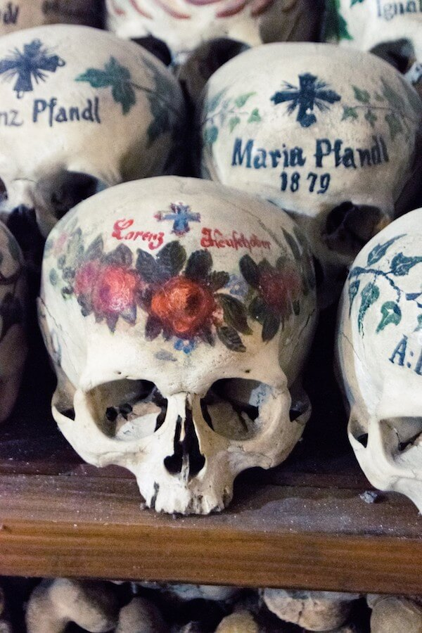 Painted skulls at the Hallstatt ossuary (Beinhaus) with a cross and a name.