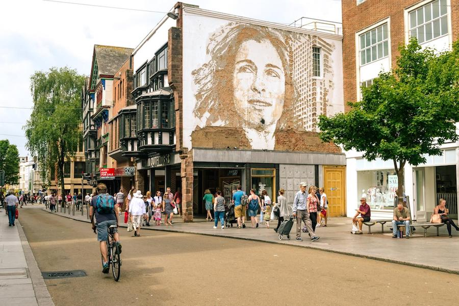 Scenic street view of downtown Exeter, Devon, United Kingdom with a mural.