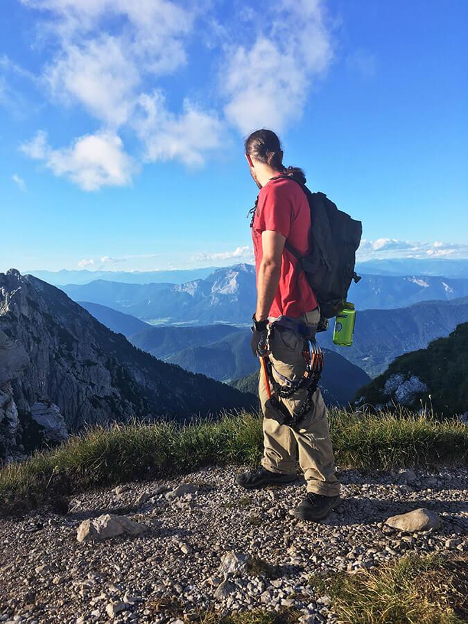 Man wearing via ferrata (klettersteig) gear admiring the view from Mangart Saddle. #travel #klettersteig #slovenia #viaferrata