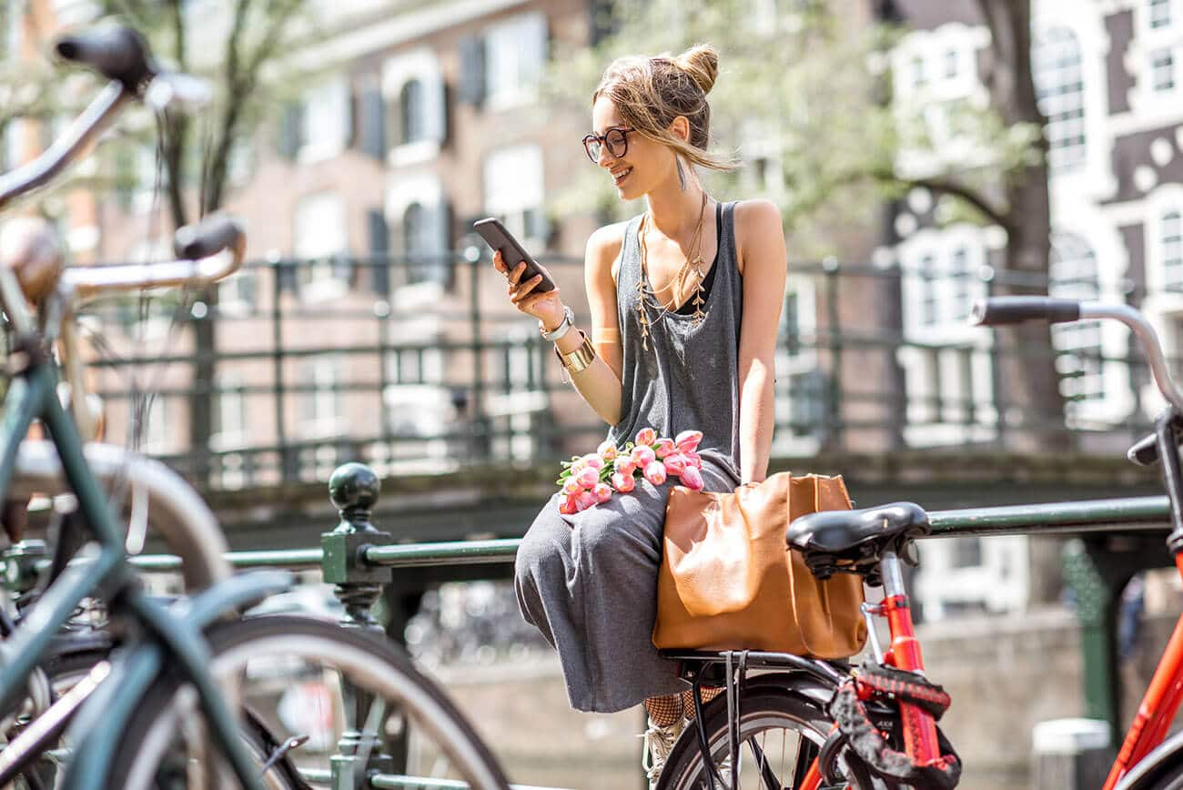 Girl using her phone to download useful Dutch phone apps for Dutch expats!