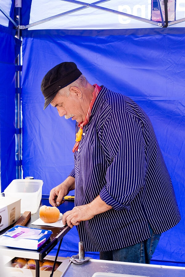 Man making a herring sandwich at Vlaggetjesdag in Scheveningen