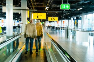 Two men traveling through Schiphol Airport in the Netherlands. Read a complete guide to Schiphol, including the best food and how to travel from Schiphol to Amsterdam.