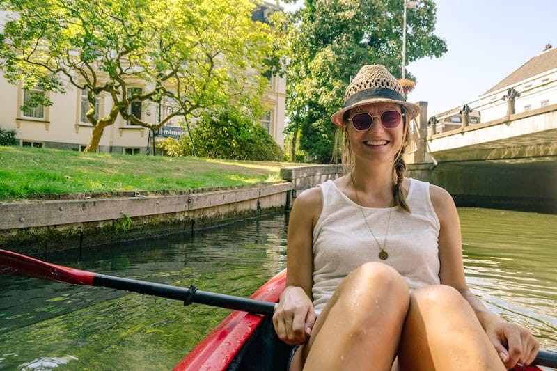Photo of a girl kayaking in Utrecht, one of the best off the beaten path things to do in Utrecht.