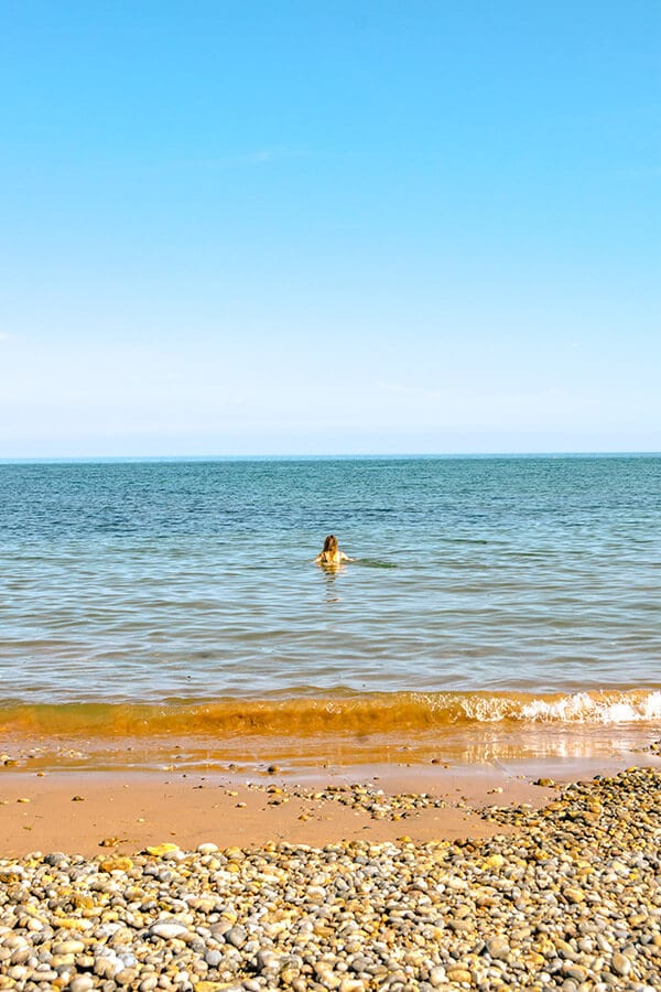 Girl swimming in the water at Ladram Bay beach