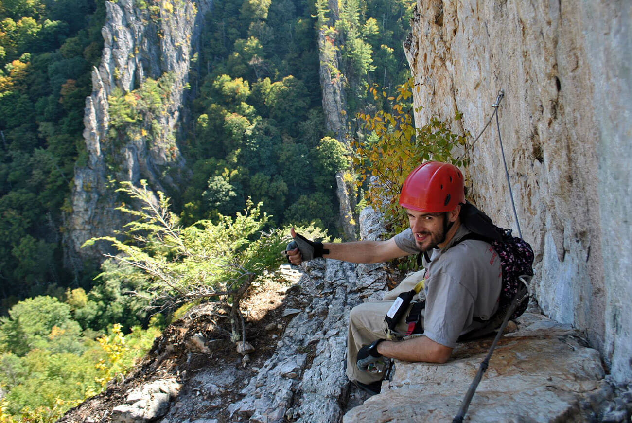 Man enjoying the stunning view from the Nelson Rocks Via Ferrata, a via ferrata in West Virginia.