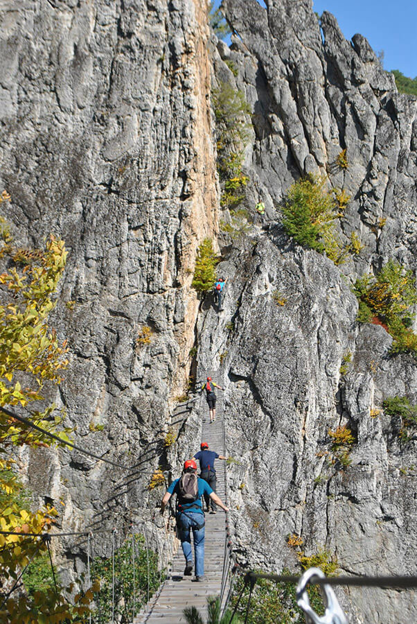 People crossing the bridge at Nelson Rocks via ferrata, perfect for lovers of rock climbing!