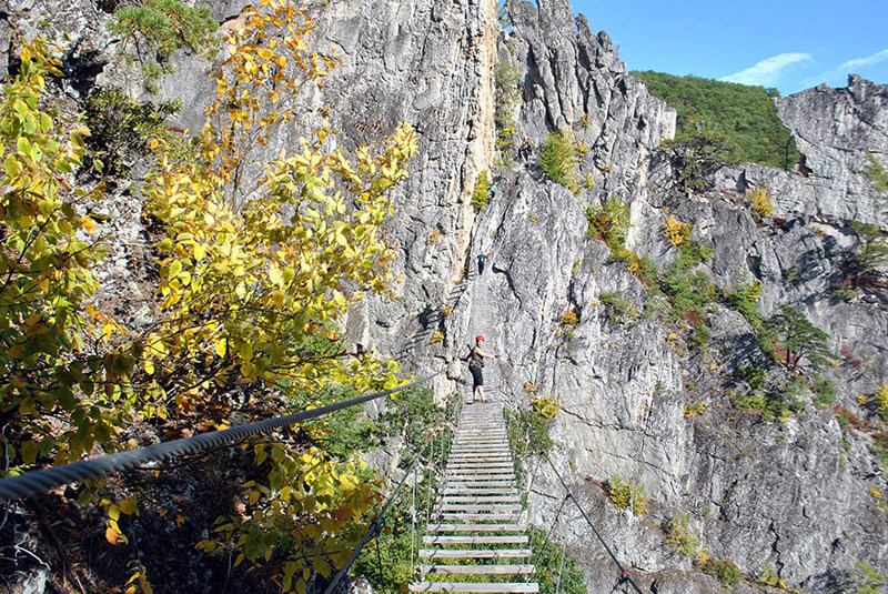 Woman walking across the bridge on the Nelson Rocks via ferrata, one of the best via ferratas in the US!