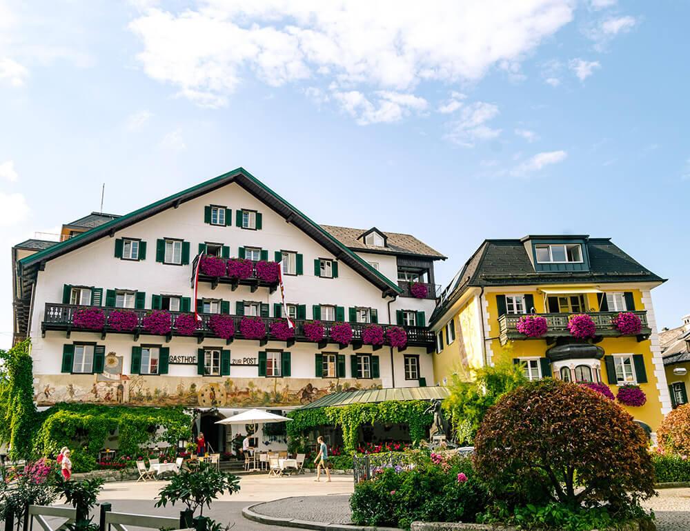 Beautiful hotel with wooden balcony and flowers in the city center of St. Gilgen.  Read where to stay in St. Gilgen, Austria!