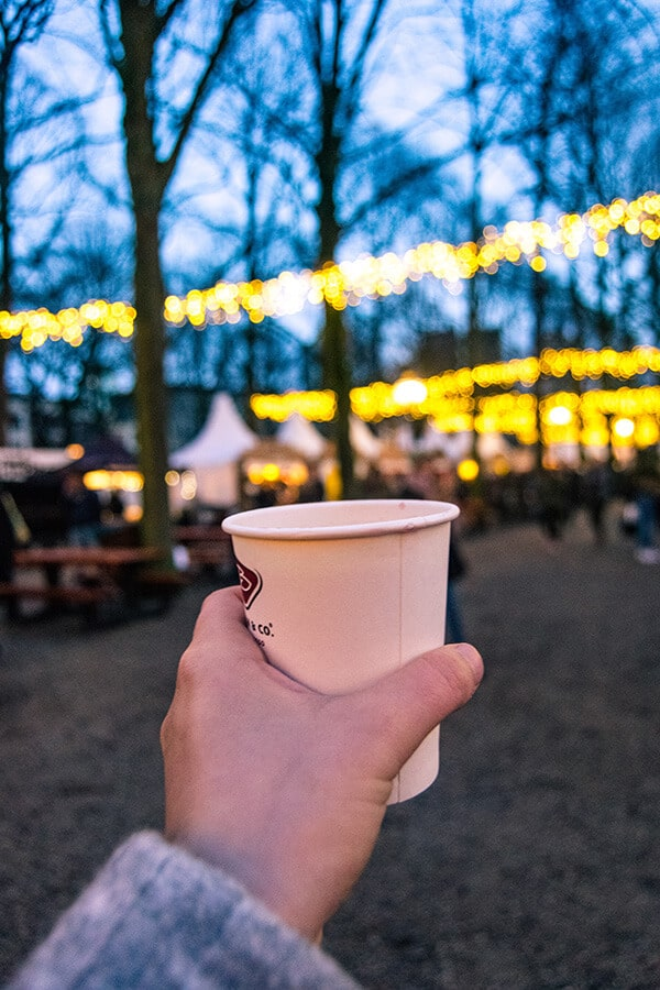 Gluhwein cup with the Royal Christmas Market in the Hague in the background.  Read about attending this Dutch Christmas market in Holland! #travel #holland #christmas #netherlands