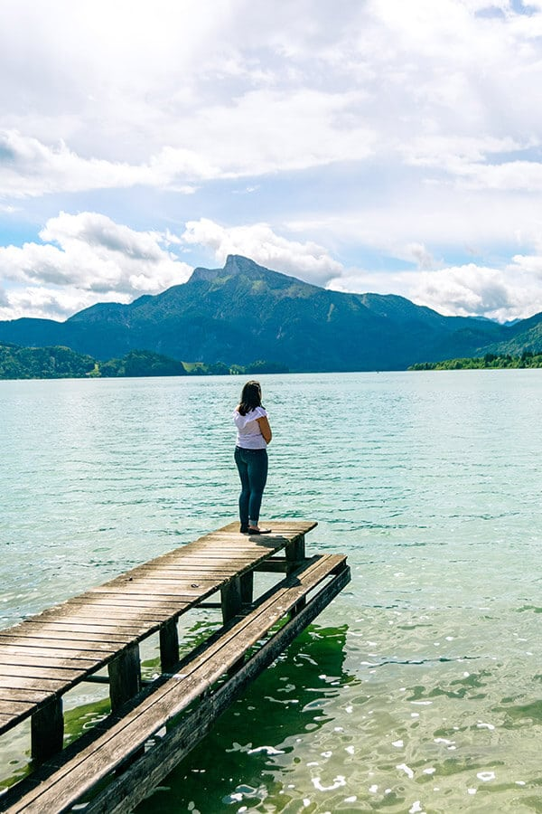 Girl admiring the beautiful view of the mountains by alpine lakes in Austria.  Read about how to save money on hotels in Austria. #travel #austria #europe