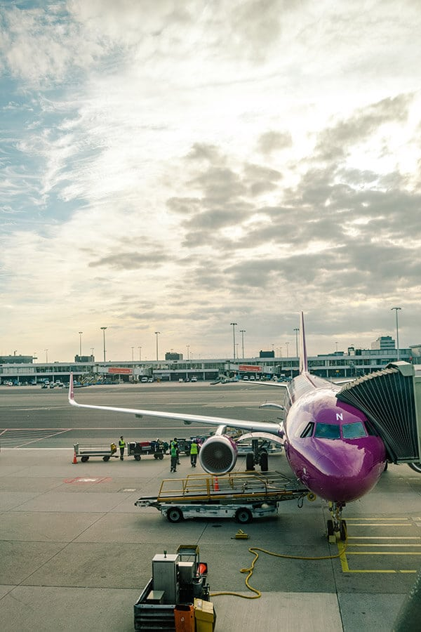WOW air plane being boarded in New York City.  This cheap airline is a great way to fly from the United States to Europe on a budget! #travel #airlines