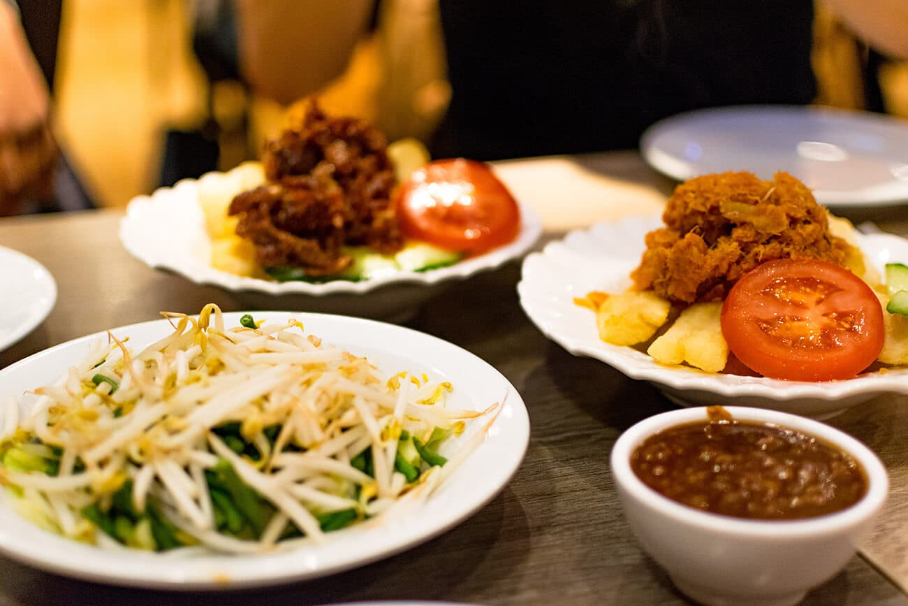 A delicious Javanese Surinamese meal shared among friends at a Surinamese restaurant in the Hague. Read about the best Surinamese food try in the Netherlands.