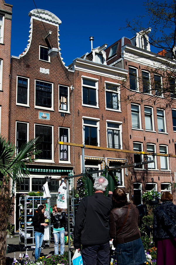 Locals and tourists browsing the weekend market in the Jordaan in Amsterdam.