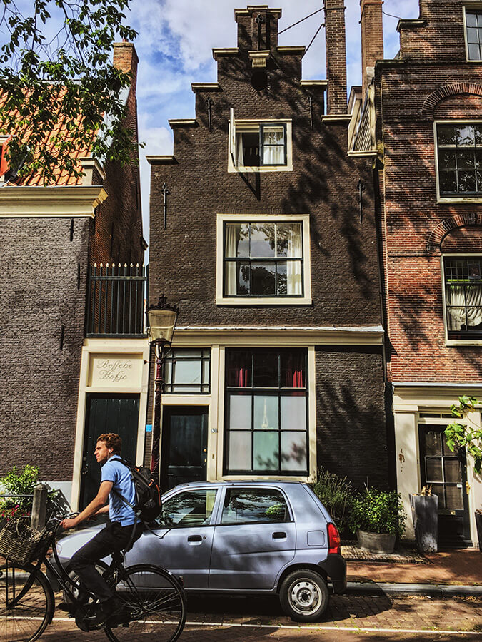 Man biking past a beautiful hofje in Amsterdam.  Follow this self-guided walking tour of the Jordaan to see secret spots in the Jordaan! #travel #amsterdam #holland #netherlands #nederland