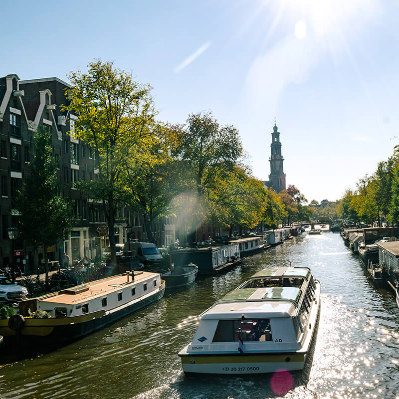 Canal boat cruising down beautiful canal (Prinsengracht) in Amsterdam.  This is the canal where Anne Frank's house is located and where you can see the Westerkerk.  #amsterdam #holland #netherlands #nederland #travel