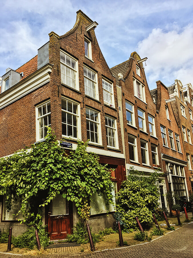 Picturesque houses in the Jordaan along a beautiful street in Amsterdam.  See the prettiest places in Amsterdam! #travel #amsterdam #holland #netherlands