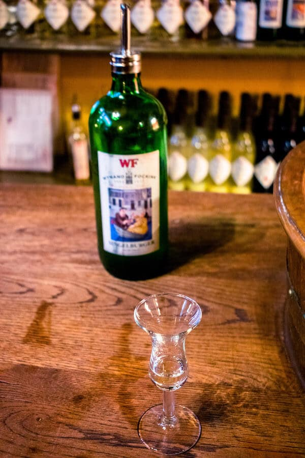 A jenever glass at a liquor tasting at Wynand Fockink, one of the best places to try genever, Dutch gin, in Amsterdam! This authentic bar dates back to the 1600s! #amsterdam #netherlands #travel