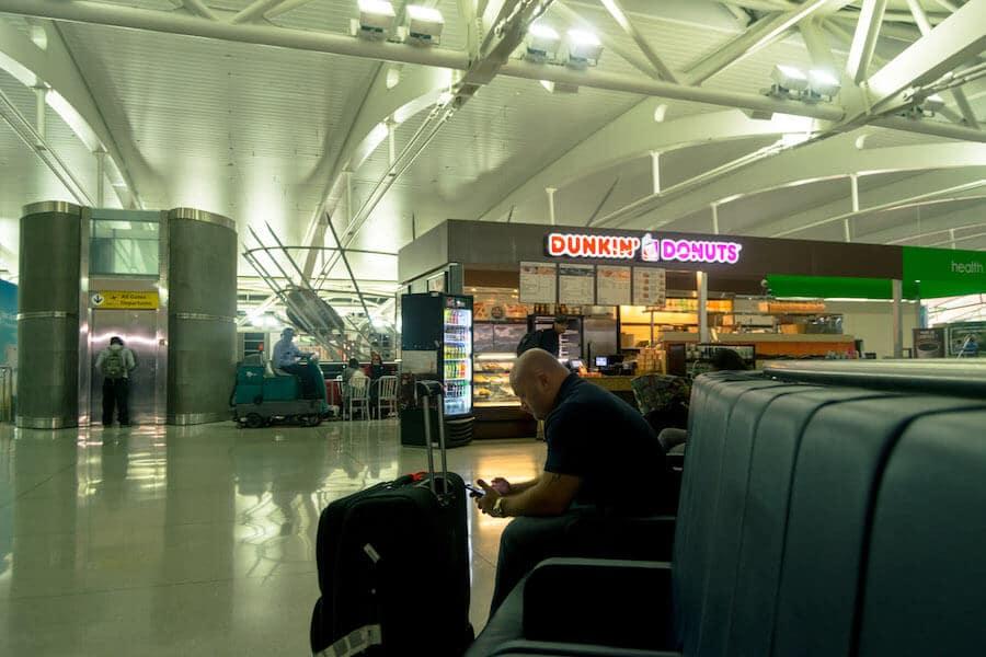 Man waiting near Dunkin Donuts at Terminal One at JFK overnight