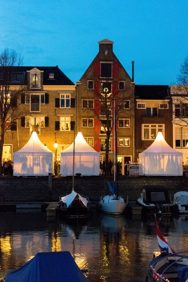 Beautiful building in Dordrecht surrounded by stalls for the Christmas market. The Dordrecht Christmas market is worth visiting! #dordrecht #holland #kerst #travel #netherlands