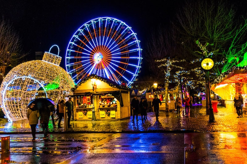 Maastricht Christmas Market at night including lit up ferris wheel and lit up Christmas ornament! This Christmas market is one of the most well-known markets in the Netherlands! #netherlands #maastricht #travel #nederland #limburg