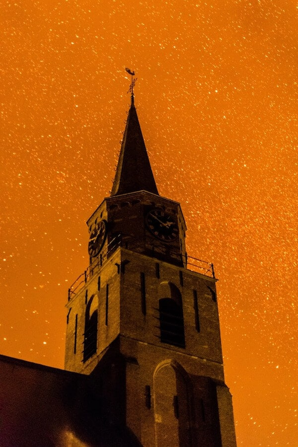 Haunting image of Scheveningen church on New Year's Eve with fire and ash....