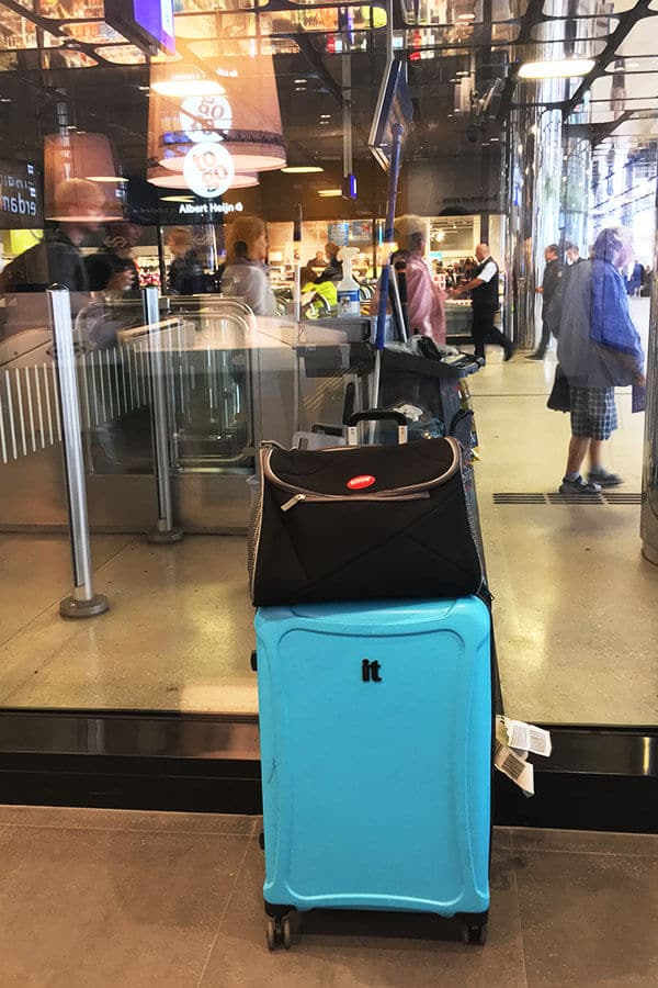 The best cat carrier for international travel on top of a rolling suitcase in Amsterdam.  Read about the most essential item for flying with your cats! #travel #cats #pettravel #cat