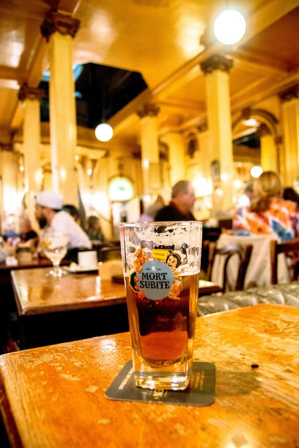 A beer at A La Mort Subtite, one of the classic places to have a beer in Brussels.  This charming cafe in Brussels has a gorgeous interior! #travel #beer #brussels #belgium