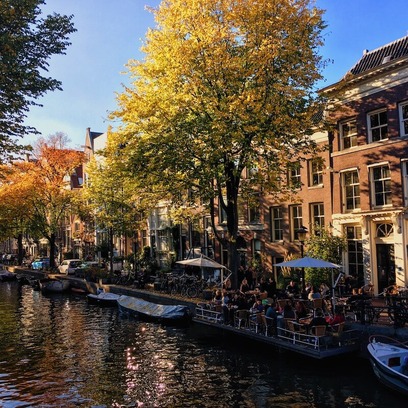 Beautiful picturesque canal in Amsterdam showing beautiful rentals.  Read how to find an apartment rental without losing your mind!