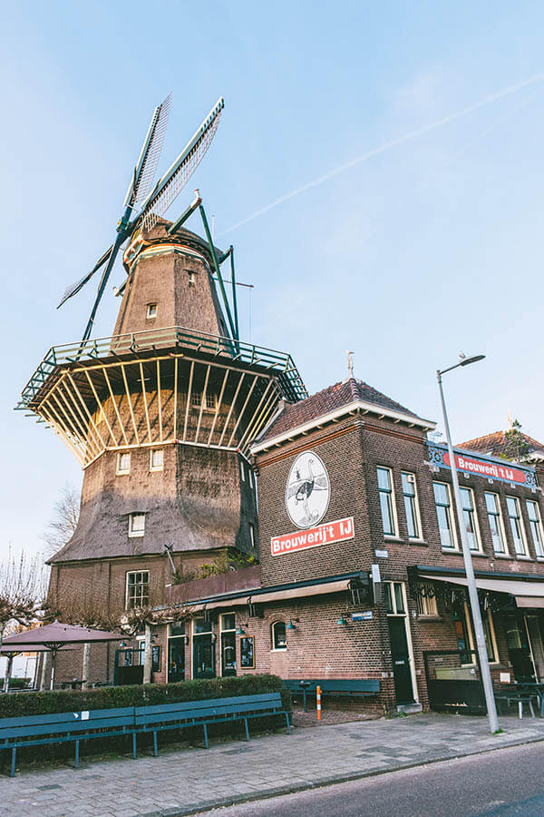Photo of Brouwerij 't IJ, the famous Amsterdam brewery next to a windmill. This craft brewery is a great place to get a beer in Amsterdam! #amsterdam #netherlands #travel #beer #windmill