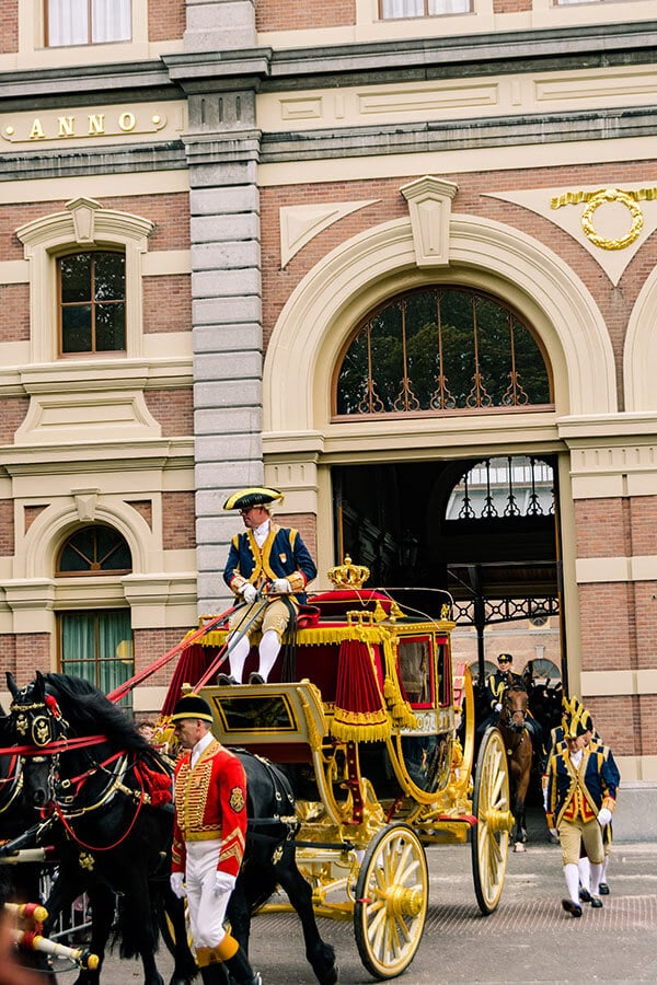 Military procession with glass carriage exiting the Royal Stables in the Hague on Prince's Day in the Hague. #haag #denhaag #hague