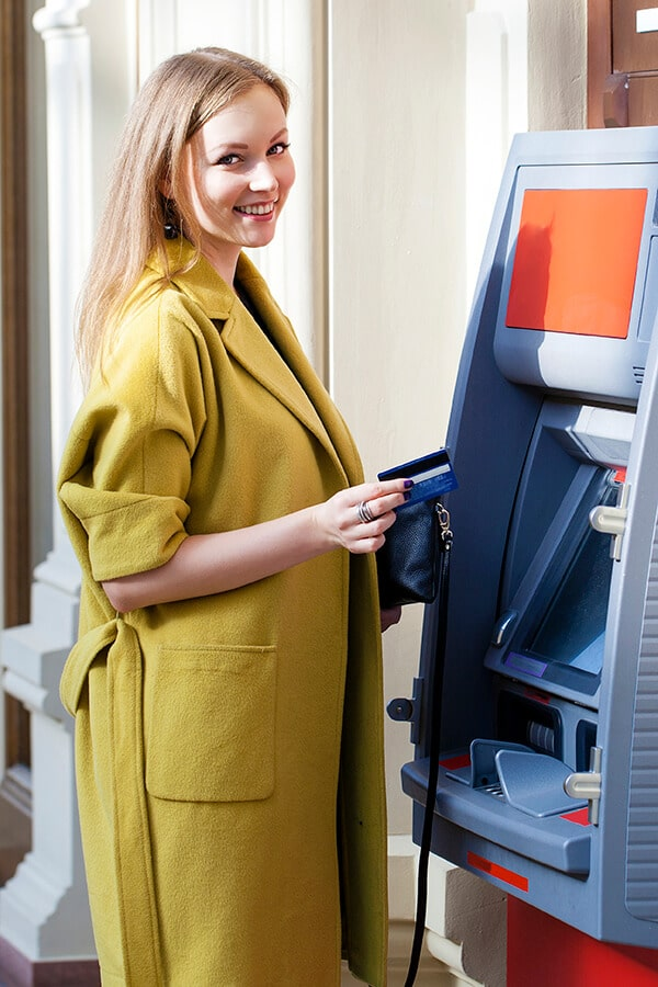 Woman using an ATM in Europe, one of the best ways to get money out in Europe with a good exchange rate! #travel #europe #money