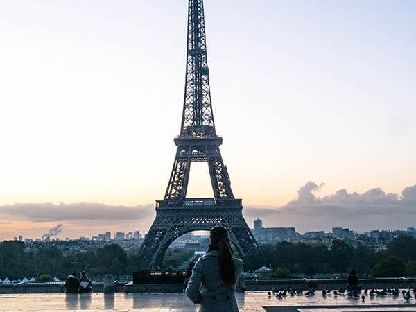 Stylish girl in front of the Eiffel Tower. Read how to dress like a local in Europe by an American living in Europe! #travel #europe #paris #fashion #style #fashionblogger