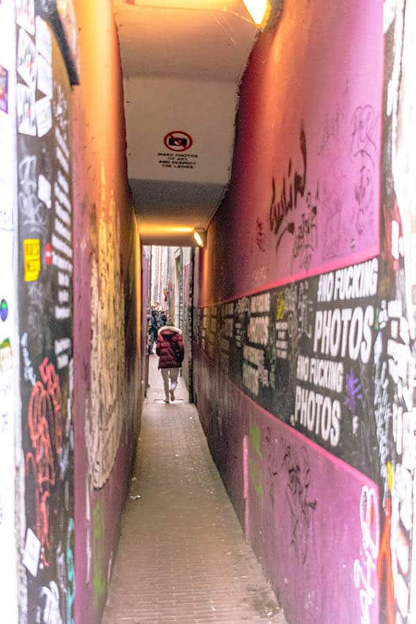 Woman entering a narrow street in the Red Light District by herself.