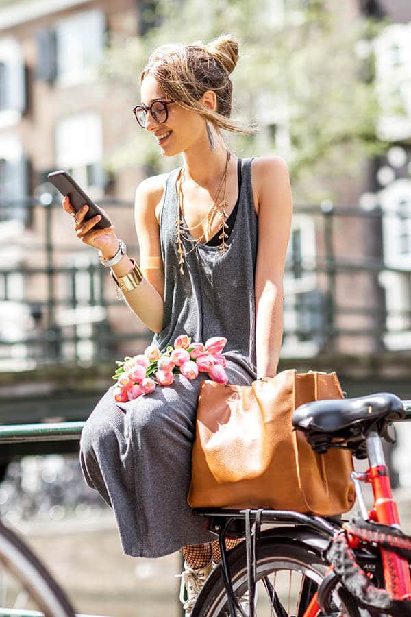 Expat woman using her mobile phone in the Netherlands after setting up her Dutch mobile phone service in Amsterdam, the Netherlands