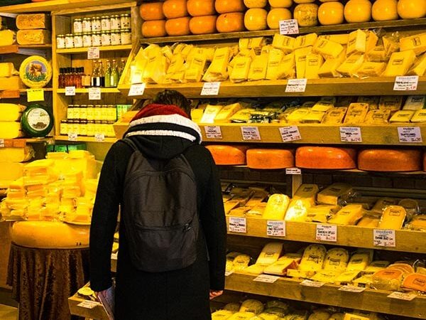 Man browsing for Dutch cheese at a small Dutch cheese shop in Amsterdam, one of the best places to sample Gouda, Edam, and other cheeses!
