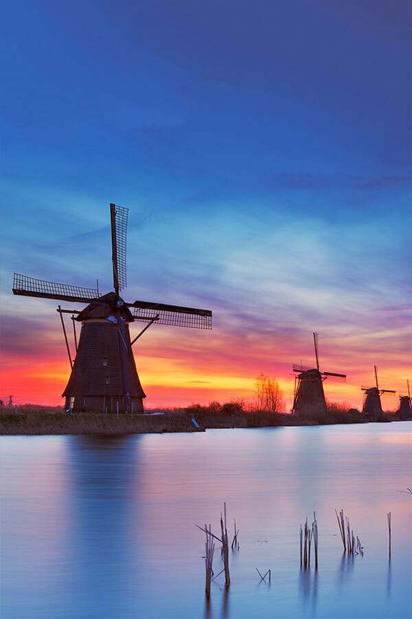 Beautiful Dutch windmills at sunset at Kinderdijk, one of the most beautiful places in Holland!