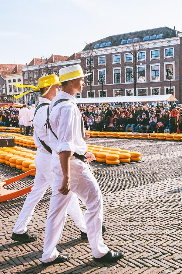 Two Alkmaar cheese carriers that are part of the cheese guild in Alkmaar in traditional clothing