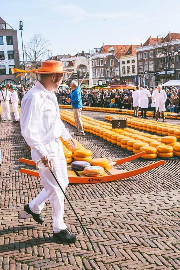 The Cheese Father of the Alkmaar Cheese guild wearing traditional orange hat and carrying a cane.  He is presiding over the Alkmaar Cheese Market!