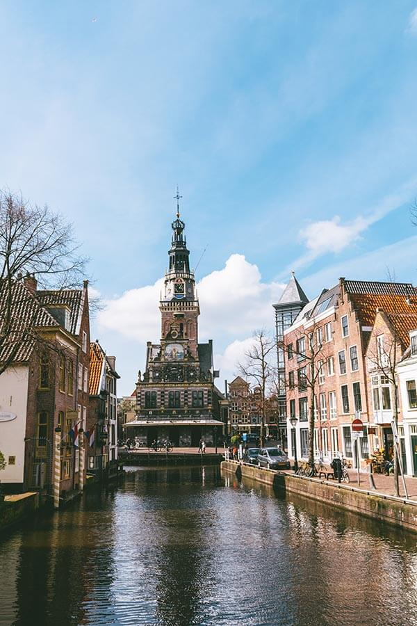 Beautiful view of canal houses and Alkmaar Cheese Market Square over a canal.