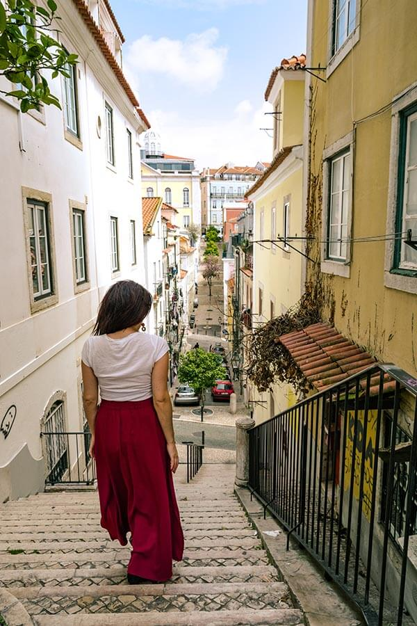 Girl walking down scenic street in Lisbon.