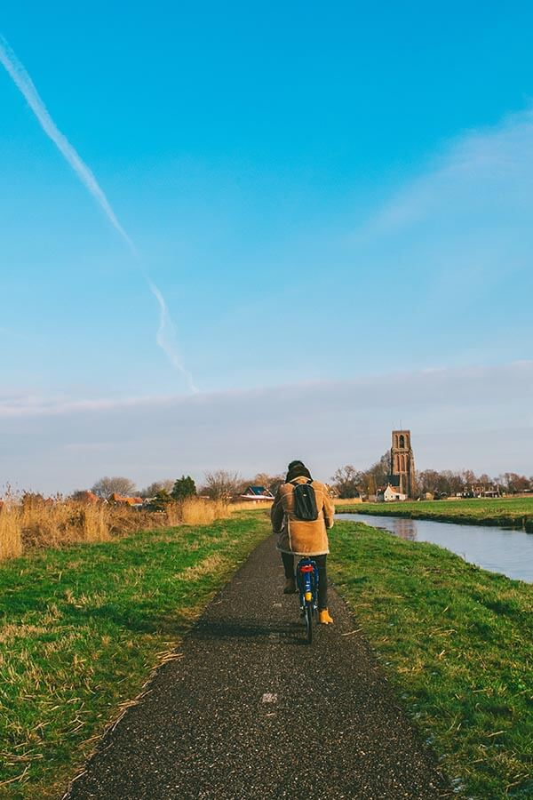 Man cycling in the Dutch countryside outside of Amsterdam.  See the most beautiful places in Holland!