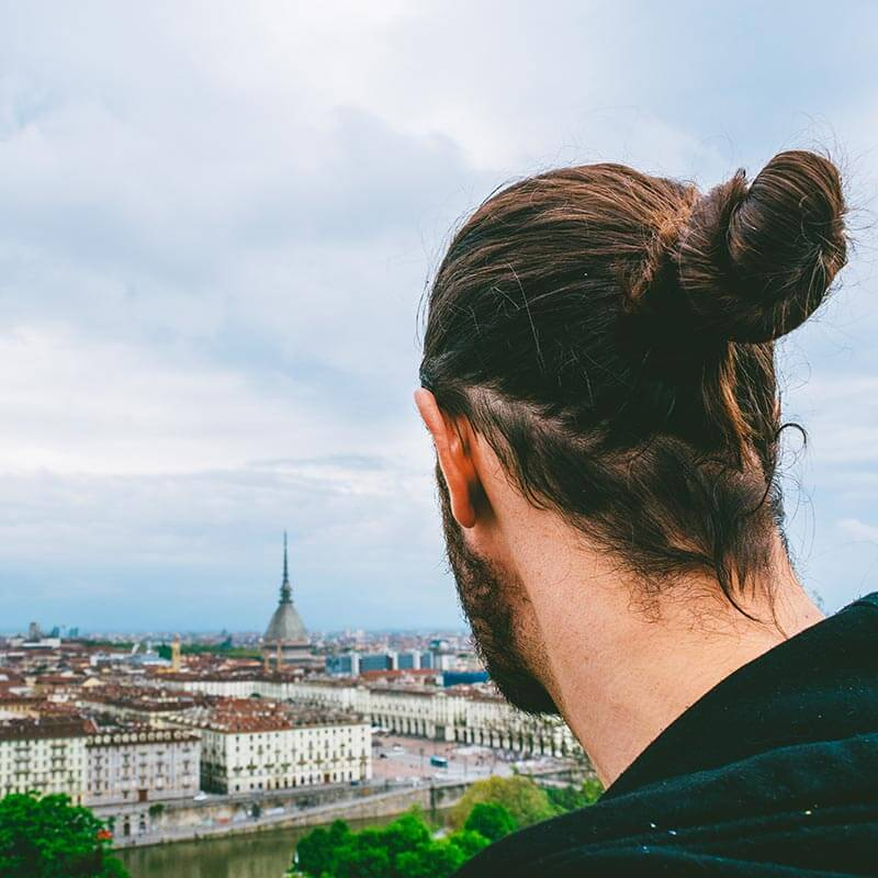 Man enjoying a beautiful view of Turin from a nearby mountain
