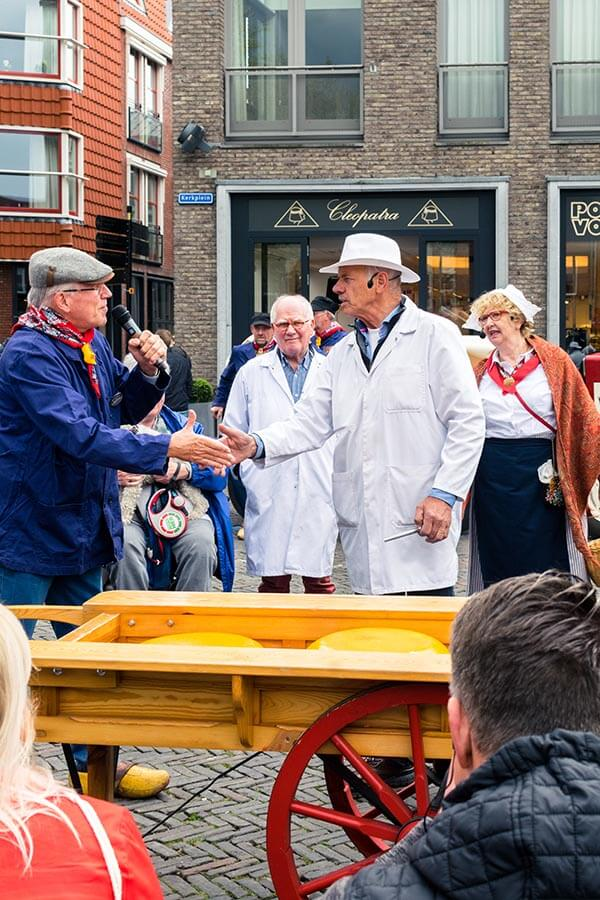 Two men debating the price of cheese in the Netherlands at the Woerden Cheese Market, one of the best things to see in Woerden